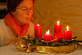 Woman blowing out four candles at advent wreath