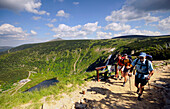 Hikers on a hiking trail above the Lake Malego, Bohemian mountains, Lower Silesia, Poland, Europe