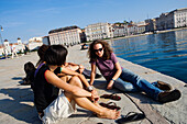 A group of young people at the harbour, Molo Audace and Piazza dell'Unita d'Italia in the background, Trieste, Friuli-Venezia Giulia, Upper Italy, Italy