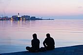 Two men sitting on Molo Audace, Molo Bersaglieri in the background, Trieste, Friuli-Venezia Giulia, Upper Italy, Italy