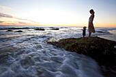 Mutter und Kind auf einem Felsen am Meer bei Sonnenuntergang, Punta Conejo, Baja California Sur, Mexiko, Amerika