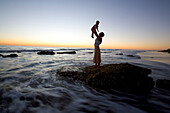 Mother and child on a rock on the waterfront at sunset, Punta Conejo, Baja California Sur, Mexico, America