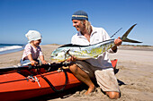 A man showing his little daughter his recently caught mahi-mahi, Punta Conejo, Baja California Sur, Mexico, America