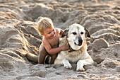 Kleines Mädchen spielt im Sand mit einem Hund, Punta Conejo, Baja California Sur, Mexiko, Amerika