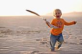 Kleines Mädchen läuft mit einer Feder in der Hand über den Sandstrand, Punta Conejo, Baja California Sur, Mexiko, Amerika