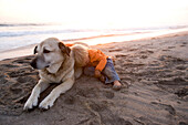 Little girl hugging her dog on the beach at sunset, Punta Conejo, Baja California Sur, Mexico, America
