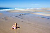 Little girl sitting on the beach in the sunlight, Punta Conejo, Baja California Sur, Mexico, America