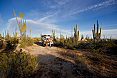 A family standing in front of a school bus amidst cactuses in the desert, Catavina, Baja California Sur, Mexico, America
