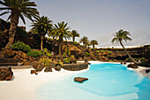 Swimming pool with palm trees near a volcanic cave, Jameos del Agua, hollow lava tunnel, architect Cesar Manrique, UNESCO Biosphere Reserve, Lanzarote, Canary Islands, Spain, Europe