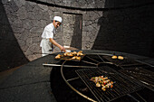 Cook cooking food on a volcanic grill, volcanic heat, Timanfaya Restaurant, architect Cesar Manrique, Parque Nacional de Tiimanfaya, Montanas del Fuego, Lanzarote, Canary Islands, Spain, Europe