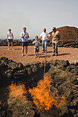Demonstration of fire by volcanic heat with brushwood, Parque Nacional de Tiimanfaya, Montanas del Fuego, park ranger, family, UNESCO Biosphere Reserve, Lanzarote, Canary Islands, Spain, Europe