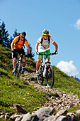 Man and woman riding mountain bikes downhill, Spitzingsee, Bavaria, Germany