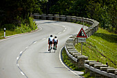 Two racing cyclists on bendy road, Spitzing, Bavaria, Germany