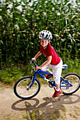 Girl (6-7 years) riding bicycle, Bavaria, Germany