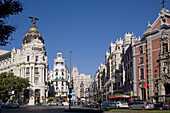 Spain,  Madrid,  Centro,  busy intersection of Gran Via and Calle Alcalár with Edificios Metropolis and Grassy and the prominent ornamental facade of Iglesia de San José,  San José Church