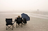Weather,  fog,  expecting the sun,  woman,  newspaper,  chairs,  trolley,  umbrella,  St.Peter-Ording,  Schleswig-Holstein,  Germany