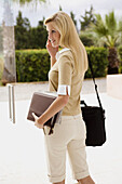 Adult, Adults, Blonde, Blondes, Briefcase, Briefcases, business, Businesspeople, Businessperson, Businesswoman, Businesswomen, calling, Carry, Carrying, Caucasian, Caucasians, Cell phone, Cell phones, Cellular phone, Cellular phones, Color, Colour, Commun