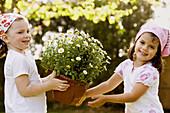 Aussen, Blume, Blumen, Blumentopf, Blumentöpfe, Draussen, Farbe, Freizeit, Freude, Freund, Freunde, Freundin, Freundinnen, Freundschaft, Garten, Gärten, Gartenarbeit, Glück, Glücklich, Halbfigur, Halten, Kind, Kinder, Kindheit, Kleinkind, Kleinkinder, Kop