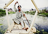 an amazing movement shot of a man paddling a boat on Dahl lake India.