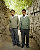 two well dressed indian boys on their way to school.