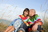 Adult, Adults, Affection, beach, beaches, Blanket, Blankets, Bond, Bonding, Bonds, Caucasian, Caucasians, Color, Colour, complicity, Contemporary, couple, couples, Cover, Covering, Daytime, exterior, female, Fondness, Grass, Grasses, grin, grinning, happi