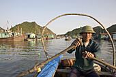 Fisherman at floating fishing village at the Halong Bay at the Gulf of Tonkin, Vietnam, Asia