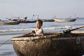 Vietnamese boy in a fishing boat on the beach, Mui Ne, Binh Thuan Province, Vietnam, Asia