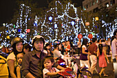 Young vietnamese family in front of christmas decoration downtown Saigon, Hoh Chi Minh City, Vietnam, Asia
