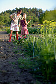 Mother and daughter (8-9 years) in vegetable garden, Lower Saxony, Germany