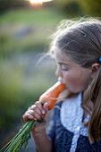 Girl (8-9 years) eating a carrot, Lower Saxony, Germany