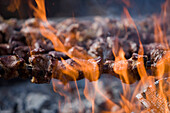 Grilling Espetada beef skewer kebabs over an open fire at a religiois festival, Ponta Delgada, Madeira, Portugal
