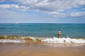 Woman going for a swim on Porto Santo Beach with Porto Santo Line Ferry Lobo Marinho on the horizon, Porto Santo, near Madeira, Portugal