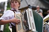 Boy playing accordion, Styria, Austria