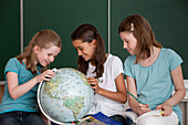 Schoolgirls with globe in classroom, Hamburg, Germany