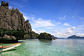 Boat on shore of an uninhabited limestone island in the sunlight, Bacuit Archipelago, El Nido, Palawan, Philippines