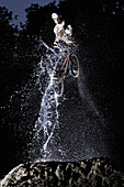 BMX bike rider jumping through water jet, Mindelheim, Bavaria, Germany