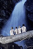 Four naked persons sitting on trunk in front of a waterfall, See, Tyrol, Austria