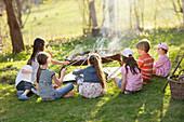 Children barbecueing sausages, Munsing, Bavaria, Germany