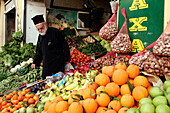 Orthodox Priest In Front Of A Fruit And Vegetables Stall, Crete, Greece