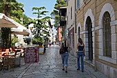 Young Teenagers, Tourists In The Street Near The Port In The Town Of Porec, Istria, Croatia