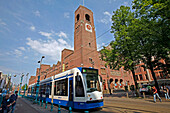 Tramway On Damrak Street And Beurs Van Berlage Designed By H. P. Berlage, Very Imposing With Its 141 Meters Of Red Brick Facade Along The Damrak. Seat Of The Netherlands Philharmonic Orchestra, The Big Hall With Perfect Acoustics Hosts Concerts And Other