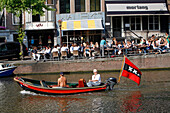 Boat With The Flag With Three Crosses, Emblem Of The City Of Amsterdam, And Cafe Walem Keizersgracht, Netherlands, Holland
