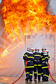 Firefighters Approaching A Fire. Training Of The Firefighters Of The Sdis38 In Hydrocarbon Fires, Gesip (Study Group Of Safety In The Petrol And Chemical Industries) Of Roussillon, Isere (38), France