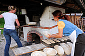 Two women baking breads, Hefteralm, Chiemgau Alps, Upper Bavaria, Bavaria, Germany