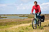 Woman cycling, Beltringharder Koog, Nordstrand, Schleswig-Holstein, Germany