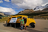 Family in front of a old snow mobile,  Icefields Parkway, Columbia Icefield, Jasper National Park, Alberta