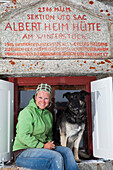 Woman and dog in front of a Albert Heim mountain lodge, Urner Alps, Canton of Uri, Switzerland