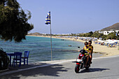 Young couple on scooter in front of beach in the sunlight, island of Naxos, the Cyclades, Greece, Europe