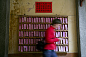 Buddhist temple, European woman passing a shelf with pink paper notes with religious sayings, Jinfeng, Changle, Fujian, China, Asia