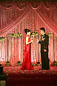 Bridal couple on a stage at a traditional chinese wedding, Jinfeng, Changle, Fujian province, China, Asia